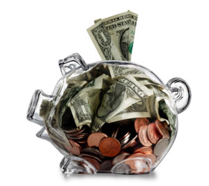 Clear piggy bank stuffed with coins and cash